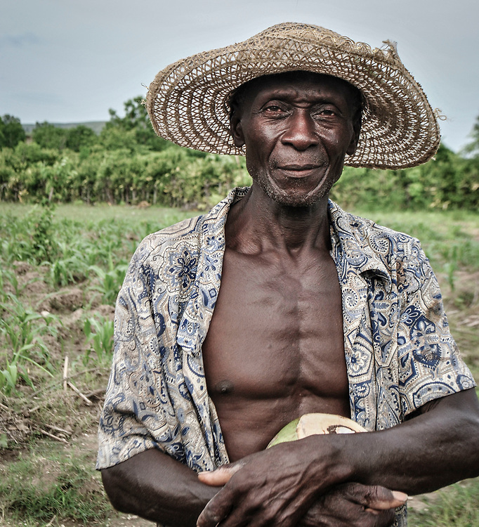 A Haitian farmer takes a break from work to keep his field from eroding in a summer of endless rain. Deslandes, Haiti