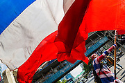 """09 MAY 2014 - BANGKOK, THAILAND: An anti-government protestor waves a Thai flag in the Ratchaprasong intersection of Bangkok. Thousands of Thai anti-government protestors took to the streets of Bangkok Friday to start their """"final push"""" to bring the popularly elected of government of Yingluck Shinawatra. Yingluck has already been forced out by a recent court ruling that forced her to resign and she is facing indictment by the National Anti Corruption Commission of Thailand for alleged improprieties related to a government rice price support scheme. The protestors Friday were marching to demand that she not be allowed to return to politics. The courts have not banned her party, Pheu Thai, which has formed an interim caretaker government to govern until elections expected in July, 2014. Suthep Thaugsuban, secretary-general of the People's Democratic Reform Committee (PDRC),  said the president of the Supreme Court and the new senate speaker, who would be selected Friday, should set up an """"interim people's government and legislative assembly."""" He went onto say that if they didn't, he would.     PHOTO BY JACK KURTZ"""
