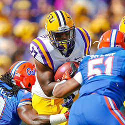 Oct 12, 2013; Baton Rouge, LA, USA; LSU Tigers running back Kenny Hilliard (27) breaks a tackle by Florida Gators linebacker Ronald Powell (7) during the first quarter of a game at Tiger Stadium. Mandatory Credit: Derick E. Hingle-USA TODAY Sports