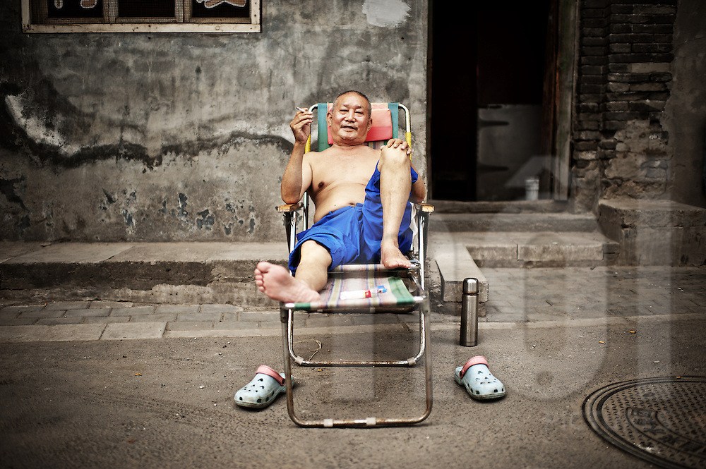 Cool old man relaxing in a traditonal Hutong street in Beijing, China