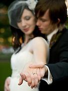 Bride and groom in the Park Blocks in Portland Oregon looking at wedding rings