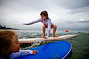 William DeShazer/Staff<br /> Nicole Kuhl, 7, left, of Naples makes her way out to catch a wave while Kate Dreyfuss, 7, of Naples attempts to ride a wave in during Ocean Kids Summer Beach Camp at Lowdermilk Park on Thursday June 21, 2012.