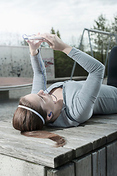 Young woman taking a break after exercising and checking sports test results on mobile phone, Bavaria, Germany
