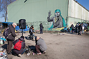Calais, France, 27 Februari 2015, With Hope for Everyone, Grafittyartist Moirione, welcomes guests at Tioxide. Dom-Dom and Nana provide electricity with their generator so people can charge their mobile phones and have contact with family.