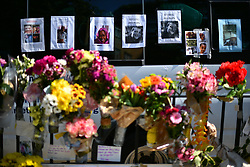 © Licensed to London News Pictures. 17/06/2017. London, UK. Posters showing the faces of people missing are seen behind flowers left at the scene of a fire at the Grenfell tower block in west London earlier this week. The blaze engulfed the 27-storey building killing 12 - with 34 people still in hospital, 18 of whom are in critical condition. The fire brigade say that they don't expect to find anyone else alive. Photo credit: Ben Cawthra/LNP