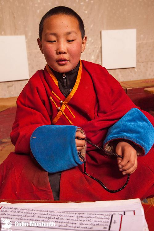 Young monk recites prayers, fingers prayer beads, Amarbayasgalant Buddhist monastery, built 1727, Selenge province , northern Mongolia