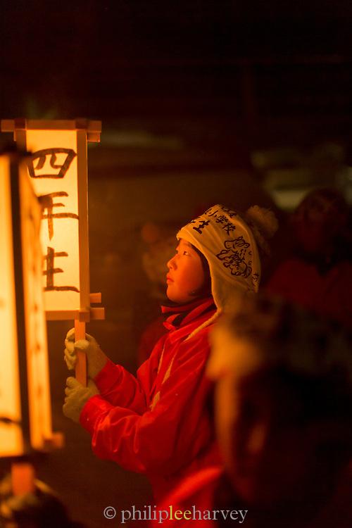 Child holding lamp on street during traditional festival, Nozawaonsen, Japan