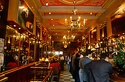 The busy atmosphere of mid-day Portuguese society inside the famous Café A Brasileira do Chiado in central Lisbon. A busy morning for locals and tourists gather in one of the world's most famous cafes located in the capital's Bica district. Standing to eat and drink it is typical of south European cultures. Opened in 1905, the Café A Brasileira (English: Café The Brazilian) is one of the oldest and most famous cafés in the old quarter of Lisbon, in the civil parish of Sacramento. Located at 120 Rua Garrett, at one end of the Largo do Chiado (Chiado Square), in the district of the same name, near the Baixa-Chiado metro stop and close to the University, ensuring its café and terrace are never empty