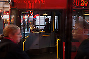 Commuters on number 24 red bus at stop in Charing Cross Road in central London.