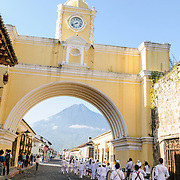 A marching band goes under the arhe at the Santa Catalina in Antigua, Guatemala.