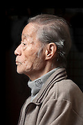side view portrait of elderly Japanese man with eyes open