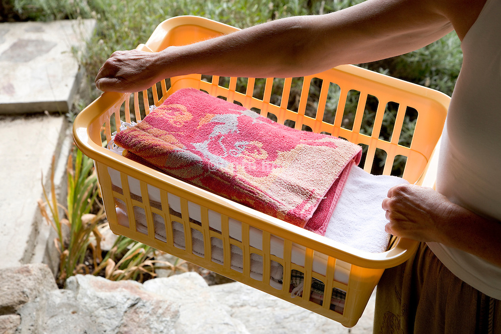 person carrying a basket with clean folded wash