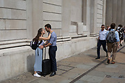 As heatwave temperatures climb to record levels - the hottest day of the year so far - a couple beneath the pillars of the Bank of England kiss in the City of London the capitals financial district aka the Square Mile, on 25th July 2019, in London, England.