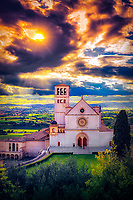 """The sun sets like fire in the sky above the Papal Basilica of St. Francis of Assisi""...<br />