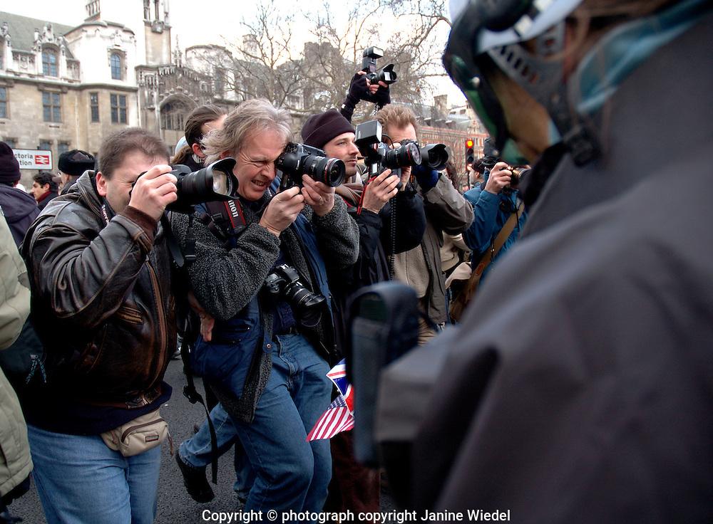 Press photographers photographing an anti-war march through london.