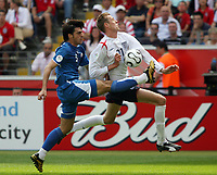 Photo: Chris Ratcliffe.<br /> England v Paraguay. Group B, FIFA World Cup 2006. 10/06/2006.<br /> Peter Crouch of England clashes with Julio Cesar Caceres of Paraguay.