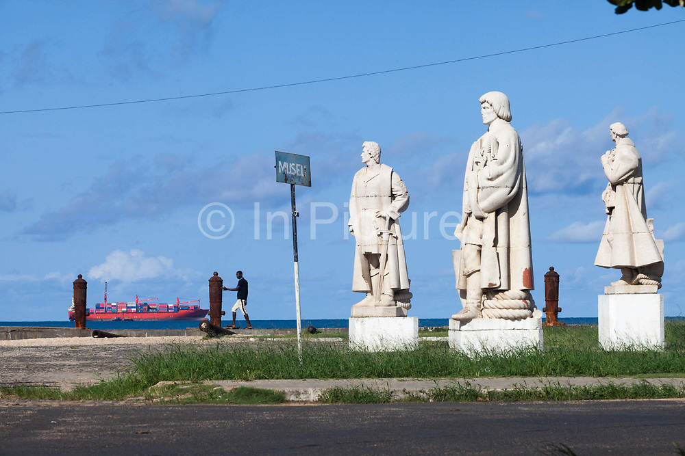 A man stands next to statues of Portuguese notables along the sea wall next to the Fort Sao Sebastiao as a shipping container passes by, Sao Tome  <br /> Sao Tome and Principe, are two islands of volcanic origin lying off the coast of Africa. Settled by Portuguese convicts in the late 1400s and later a centre for slaving, their independence movement culminated in a peaceful transition to self government from Portugal in 1975.