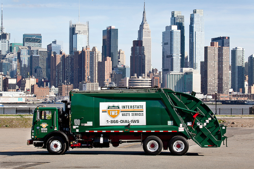 profile view of Interstate Waste Services (IWS) solid waste collection rear loader truck with the Manhattan NY skyline in background