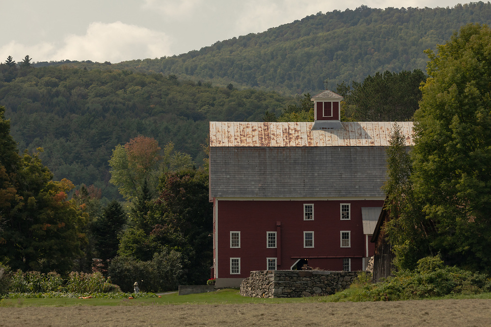 An large wooden barn nestled in the hilly farmland of Vermont.