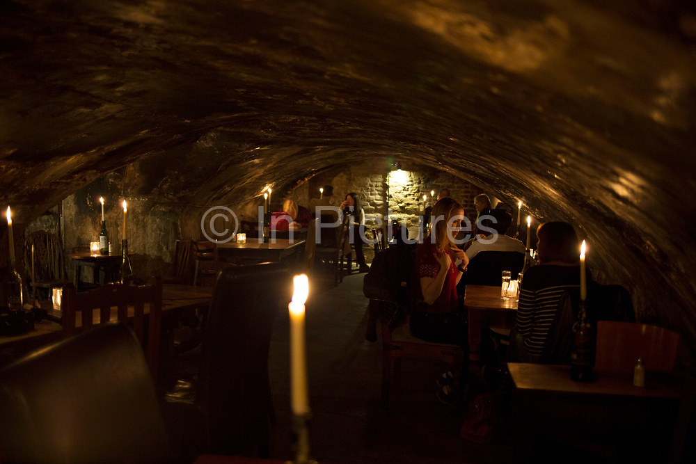 Interior of customers in Gordons Wine Bar in London, England, United Kingdom. Gordons is Londons oldest wine bar, and is in subterranean rooms with exposed brickwork, lit by candlelight in basement vaults.