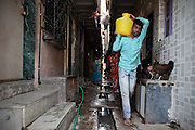 A youngster brings home some water he filled in at one of the few water sources in the slum.  The slum of Cheetah Camp on the outskirts of Mumbai, India is a predominantly muslim community on living on the fringe while the city continues to grow.