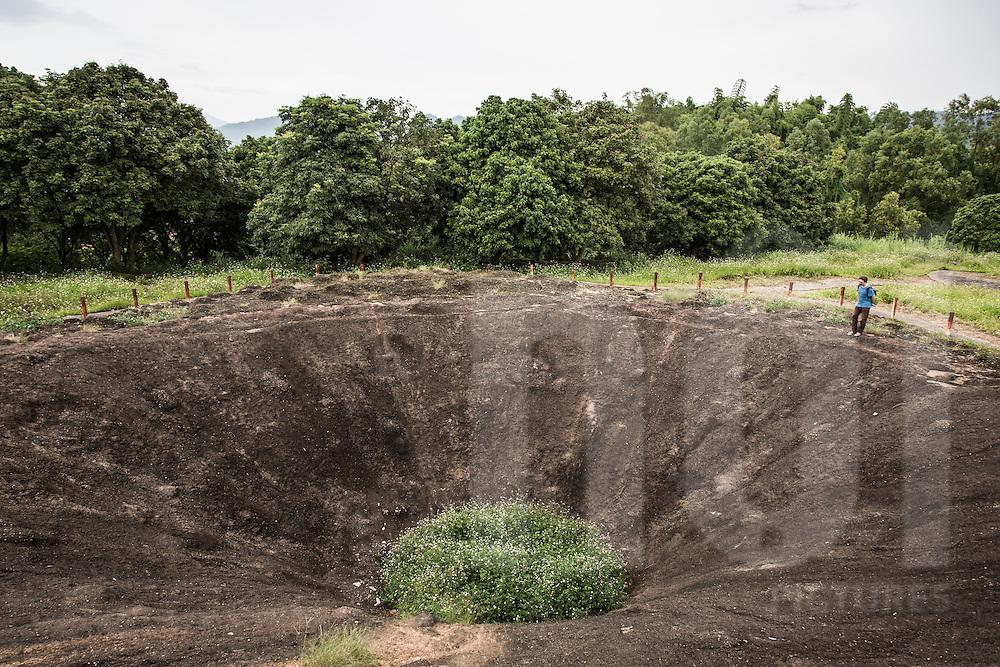 A cacausian male overlooks at a bomb crater, Hill A1 aka Eliane 2, Dien Bien Phu, Dien Bien Province, Vietnam, Southeast Asia