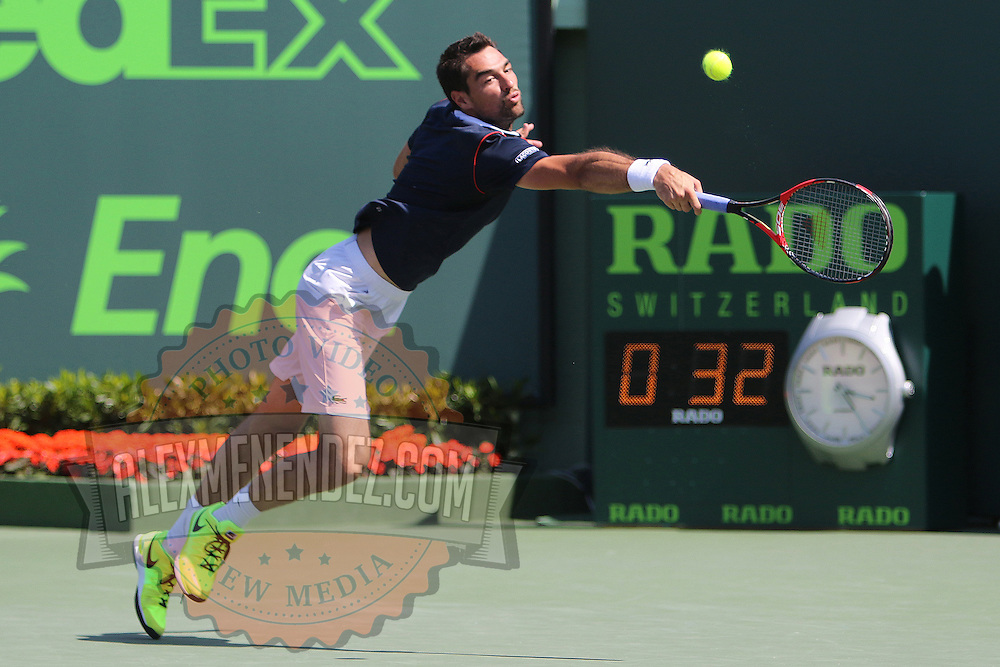 Jeremy Chardy of France misses the serve of Milos Raonic of Canada during their match at the Miami Open tennis tournament at Crandon Park on Monday, March 30, 2015 in Key Biscayne, Florida. (AP Photo/Alex Menendez)