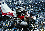 """Bill Reisland announcing """"We'll be taking off as soon as I find the Yoke and the Rudder Peddles!""""  Remains of Cessna 182 that crashed in Merrill Pass in the Alaska Range on 2-9-86.  The pilot, Michael Harbough survived with only injury being a broken ankle.  Lake Clark National Park, Alaska."""