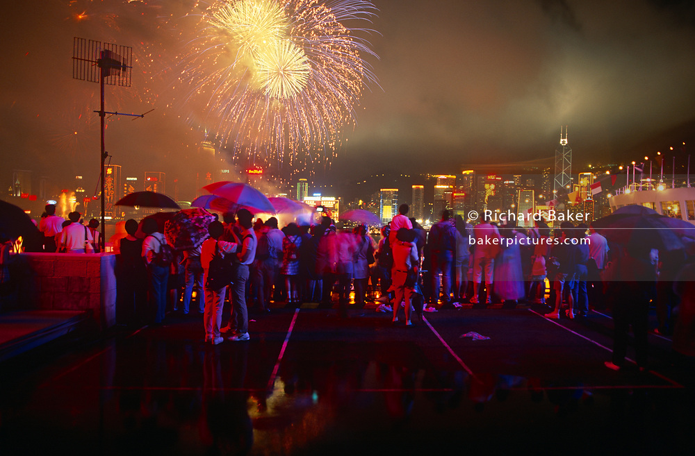 Crowds gather at the stroke of midnight beneath umbrellas to witness the transfer of sovereignty of Hong Kong from the United Kingdom to the Peoples Republic of China (PRC), on 30th June 1997, in Hong Kong, China. Midnight signified the end of British rule, and the transfer of legal and financial authority back to China. From the on the roof of Ocean Terminal shopping mall, the skyline is filled with fireworks but the glowing red comes from giant advertising lettering behind the viewer on the top floor of the building which protrudes out into Hong Kong harbour from the Kowloon side of the territory. Hong Kong was once known as 'fragrant harbour' (or Heung Keung) because of the smell of transported sandal wood.