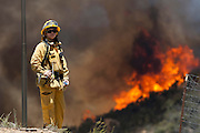 A firfighter keep watches a wildfire, Friday May 31, 2013, near Castiac, California. Fourteen aircraft and more than 550 firefighter were deployed in a ground and air campaign against a brush fire that has blackened about 1,500 acres in sparsely populated San Francisquito Canyon in the Angeles National Forest northeast of Santa Clarita. The Powerhouse Fire, which broke out Thursday afternoon, was about 15 percent contained. The estimated date of full containment is Wednesday, June 5. (Photo by Ringo Chiu/PHOTOFORMULA.com)