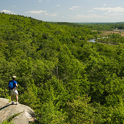A hiker on Lookout Rock in Blackstone River and Canal Heritage State Park, Uxbridge, MA. Blackstone River.  Worcester County. (MR)