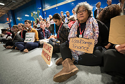 13 December 2019, Madrid, Spain: Christina Suprapti from the Asia Pacific Forum on Women, Law and Development holds a sign reading 'Loss and Damage Finance', as people gather for a sit-in demonstration at COP25, to claim space for a range a groups whose voices are not often listened to in the space of global climate negotiations: youth, women, frontline communities, indigenous communities.