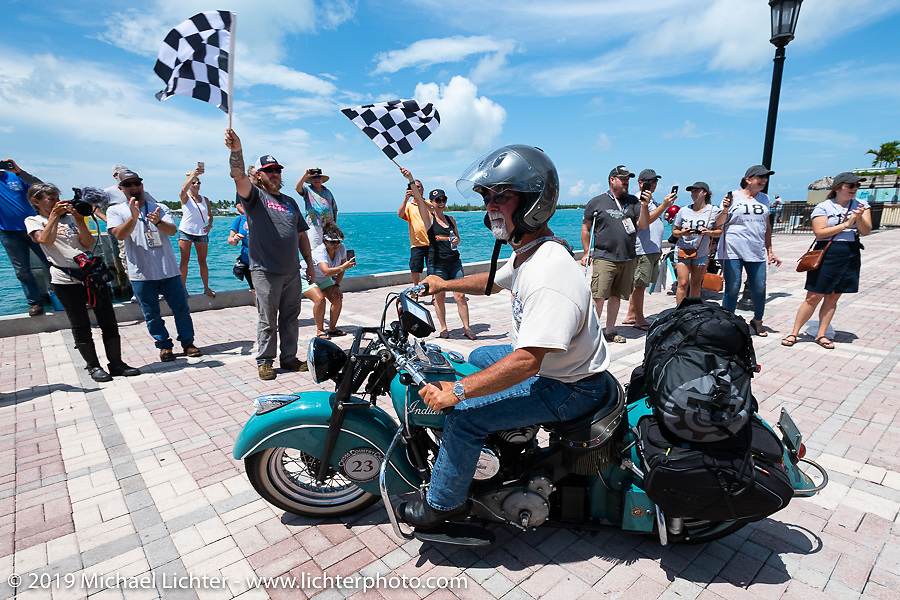 Joe Ferri riding his teal 1947 Indian Chief over the finish on the Cross Country Chase motorcycle endurance run from Sault Sainte Marie, MI to Key West, FL. (for vintage bikes from 1930-1948). The Grand Finish in Key West's Mallory Square after the 110 mile Stage-10 ride from Miami to Key West, FL and after covering 2,368 miles of the Cross Country Chase. Sunday, September 15, 2019. Photography ©2019 Michael Lichter.