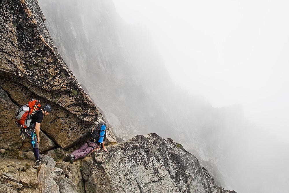 Kris Haskins watches as his climbing partner Obadiah Reid wiggles his way through an exposed notch below the West Ridge of Mount Stuart, Alpine Lakes Wilderness, Washington.