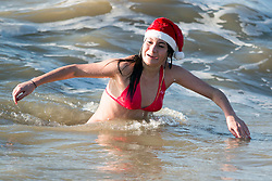 © Licensed to London News Pictures. 25/12/2014. Brighton, UK. People taking part in the traditional Christmas Day Swim in Brighton. Some dressed as Santa or Elves. The event has been cancelled by Brighton and Hove Swimming Club due to Health and Safety fears for the public. Swimmers have been warned by Brighton and Hove City Council to stay away from the sea and advised they have closed the beach to prevent people entering the sea around the Pier. Photo credit : Hugo Michiels/LNP