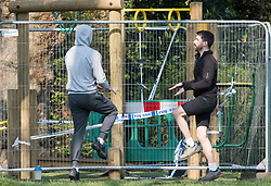 © Licensed to London News Pictures. 28/03/2020. London, UK. Two men exercising closely next to equipment cordoned off to prevent people exercising closely, at Paddington Recreation Ground in London, during a lockdown over the spread of COVID-19. Prime Minister Boris Johnson has announced that people should only leave their homes for essential work, groceries, medical necessity and exercise. Photo credit: Ben Cawthra/LNP