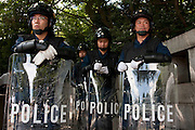 Police with riot shields and wearing riot gear at Yasukuni Shrine. On August 15th every year people gather at Yasukuni Shrine to commemorate the end of the Pacific War. Notionally a call for remembrance and continued peace it is also a Mecca for right wing nationalist including  the paramilitary Uyoku Dantai. Tokyo, Japan, August 15th 2009