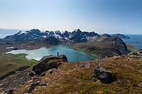 Female hikier overlooking colorful water of Flakstadpollen and surrounding mountain landscape, Flakstadøy, Lofoten Islands, Norway