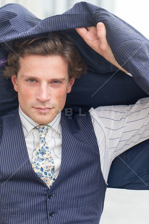 handsome man in a vest and tie with a suit jacket over his head
