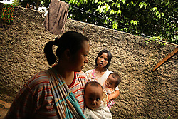 """Dian Dama Yanthi, 32, and her children, Galang, 3, and Gilang Rama, 1, with her friend Sri, 36, and her 7-month-old son Taufan, at Dian's house in Tangerang, on the outskirts of Jakarta, Indonesia, April 19, 2006. Dian had an unsafe abortion and lost her best friend to an unsafe abortion. Both took the traditional medicine """"jamu."""" Dian also had a massage from a traditional birthing attendant. Over two million abortions are performed in Indonesia every year, many by unskilled practitioners. Thousands of women survive but often with life-long disabilities. It is said by doctors and activists that a woman dies every hour in Indonesia due to unsafe abortions."""