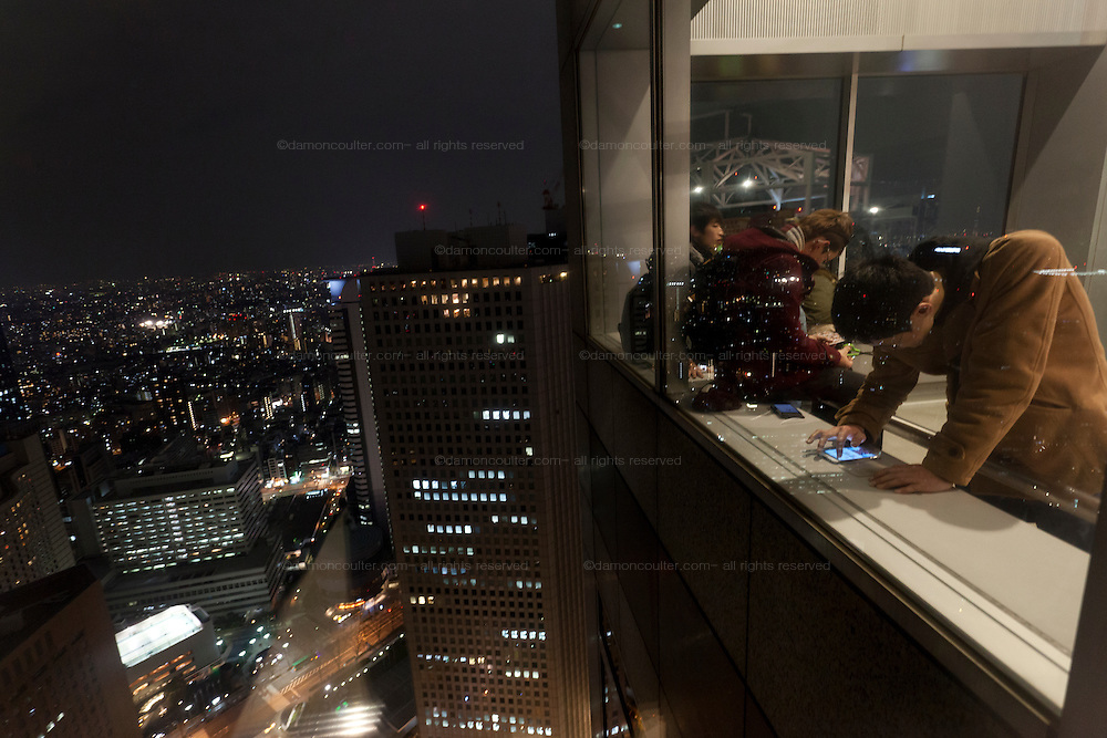 Tourists use smartphones by windows on the 45th floor obsevation floor of the Tokyo Metropolitan Government Tower, Shinjuku, Tokyo, Japan. Sunday February 23rd 2014