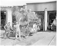 D&RGW shop men cleaning the smokebox of #492 at Durango roundhouse.  #473 is in next stall.<br /> D&RGW  Durango, CO  Taken by Payne, Andy M. - 8/6/1966<br /> A. M. Payne Collection 003-210.
