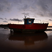 """Little red boat blue.<br /> <br /> Barmouth (Welsh: Abermaw (formal); Y Bermo (colloquial)) is a town in the county of Gwynedd, north-western Wales, lying on the estuary of the River Mawddach and Cardigan Bay. Historically in Merionethshire, the English form of the name is derived from """"Aber"""" (estuary) and the river's name """"Mawddach""""<br /> <br /> The town is served by Barmouth railway station.<br /> <br /> The town grew around the shipbuilding industry, and more recently as a seaside resort. Notable buildings include the mediaeval Tŷ Gwyn tower house, the 19th century Tŷ Crwn roundhouse prison and St John's Church.<br /> <br /> William Wordsworth, a visitor to Barmouth in the 19th century, described it thus: """"With a fine sea view in front, the mountains behind, the glorious estuary running eight miles inland, and Cadair Idris within compass of a day's walk, Barmouth can always hold its own against any rival.""""[this quote needs a citation]<br /> <br /> There is also a new Lifeboat Visitors' Centre, where visitors can purchase souvenirs, and take a look at the RNLI lifeboat from the viewing gallery. The busy harbour plays host to the annual Three Peaks yacht race.<br /> <br /> Barmouth Bridge, which takes the Cambrian Line over the River Mawddach, was also formerly at the end of the GWR Ruabon Barmouth line, which passed through Bala and Dolgellau. The southern end of the bridge is now the start of the Mawddach Trail, a cycle path and walk way that utilises the old trackbed.<br /> <br /> The Barmouth Ferry sails from Barmouth to Penrhyn Point, where it connects with the narrow gauge Fairbourne Railway for the village of Fairbourne.<br /> <br /> Barmouth is (geographically) one of the closest seaside resorts to the English West Midlands and a large proportion of its tourist visitors, as well as its permanent residents, are from Wolverhampton, Birmingham, Dudley and other parts of the Black Country, and Telford, Shropshire.<br /> <br /> In January 2014 two trains were st"""