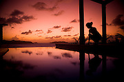A young girls admired the reflections of a sunset in a pool.