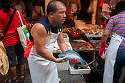A fish seller shows off a brightly coloured blue parrot fish to the gathered crowd of potential buyers at Wan Chai's thronging market on Bowrington Road. He is particularly proud of his stock of live fish of all shapes and sizes. It is perhaps surprising to westerners to see such an exotic fish for sale but in Chinese markets almost anything goes.
