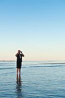 Person stands in calm shallow water of Sea of Cortez, Near San Felipe, Baja California, Mexico