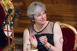© Licensed to London News Pictures. 13/11/2017. London, UK. British Prime Minister THERESA MAY swears a glucose monitor (circled in red ) on her left arm as she attends the annual Lord Mayor's Banquet at Guildhall. Mrs May was diagnosed<br />