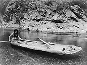 Native American Yurok Indian fisherman paddling a canoe on Trinity River.