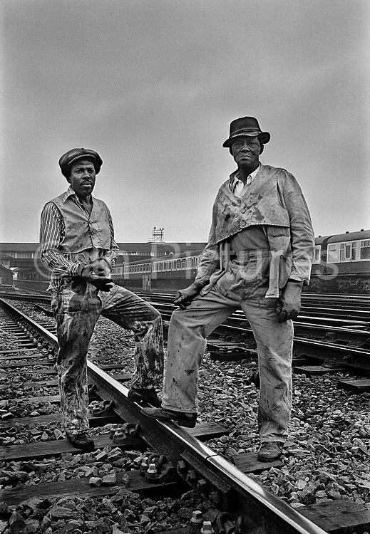 British Rail linesmen, Clapham Junction, the busiest intersection of railway line in the  in the UK. British Railways (BR), which from 1965 traded as British Rail, was the operator of most of the rail transport in Great Britain between 1948 and 1997.<br /> On 12 December 1988, three trains collided near Clapham Junction because a signal circuit had been wrongly wired. Thirty-five people died and more than 100 were injured.  Coming and Going is a project commissioned by the Museum of London for photographer Barry Lewis in 1976 to document the transport system as it is used by passengers and commuters using public transport by trains, tubes and buses in London, UK.