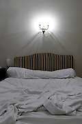 hotel bed with a turned on light above the headboard